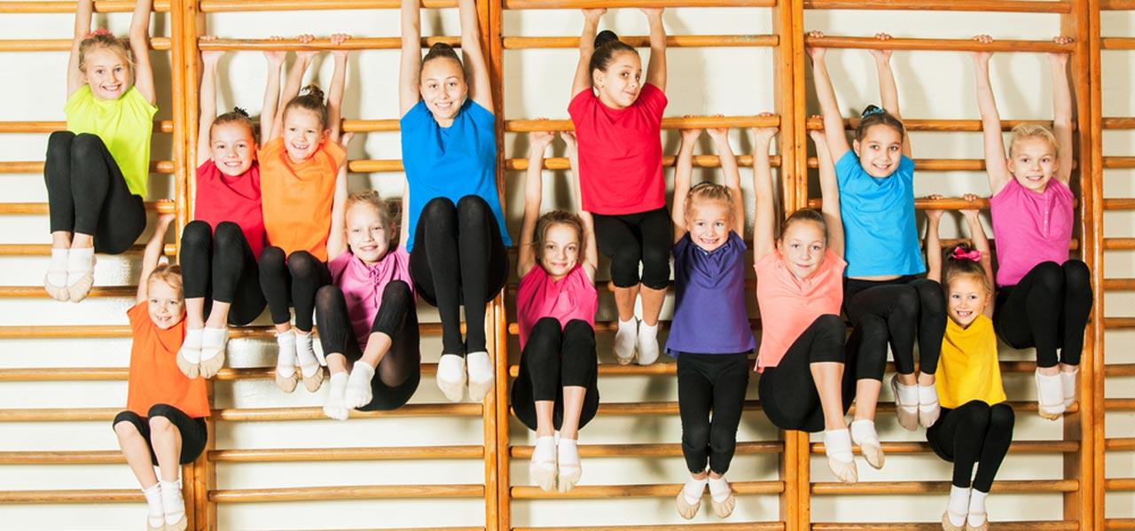 Kinder hängen an der Sprossenwand beim Zwergenturnen