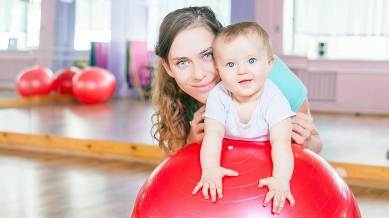 Mama hält ihr kleines Kind auf einem Gymnastikball