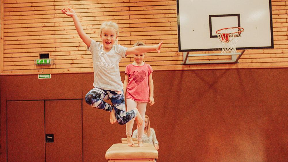 Kind springt über einen Kasten