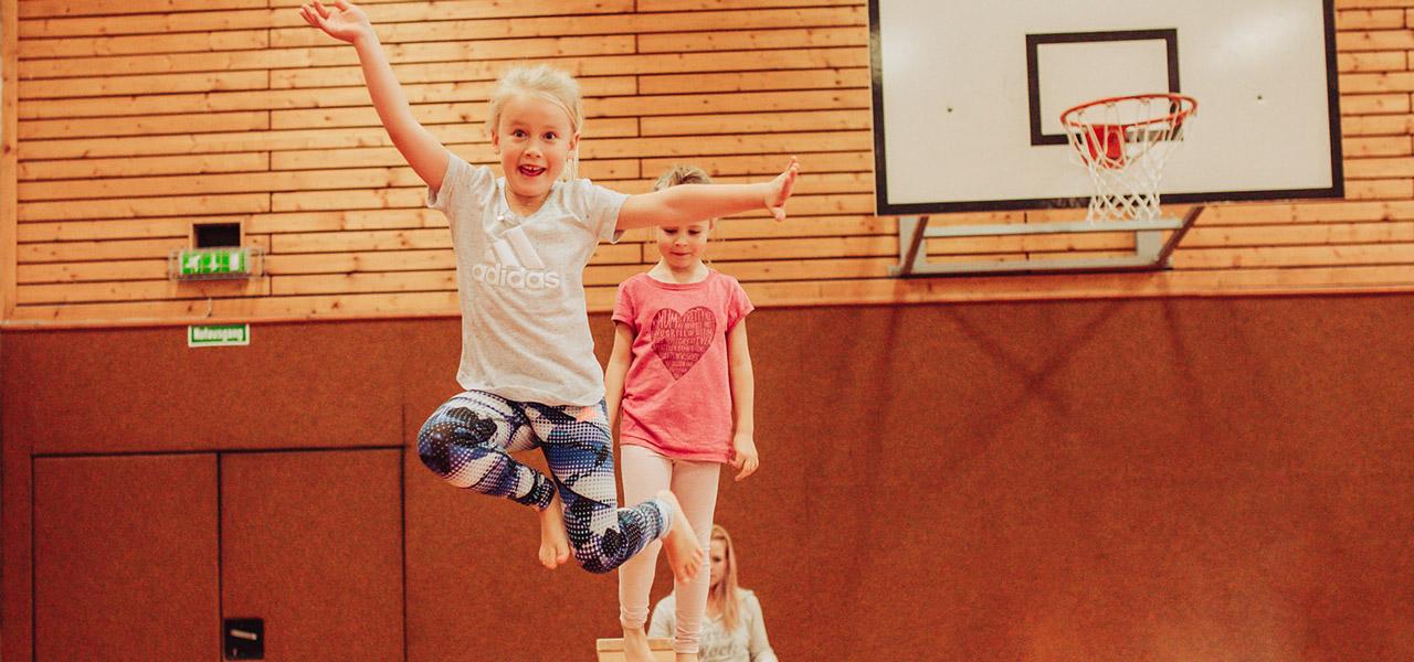 Kind springt über Kasten